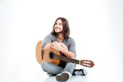 Gladlynt stilig ung man som ler och rymmer gitarren Fotografering för Bildbyråer