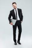 Gladlynt stiligt ungt affärsmananseende och hållande bärbar dator arkivfoto