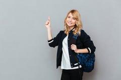 Gladlynt student för ung dam med att peka för ryggsäck arkivbilder