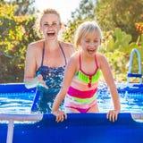 Gladlynt sund moder och dotter, i att spela för simbassäng arkivfoto