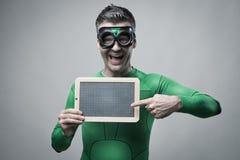 Gladlynt superhero som rymmer en svart tavla royaltyfria foton