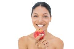 Gladlynt svart haired modell som rymmer det röda äpplet Arkivfoto