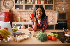 Gladlynt svart kvinna som lagar mat på köket arkivbild