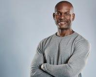 Gladlynt svart man med vikta armar i grå färger arkivfoton