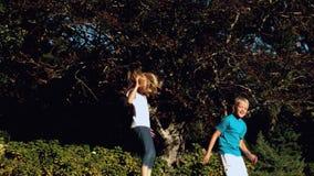 Gladlynt syskon som studsar på en trampolin arkivfilmer