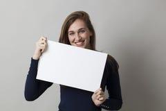 Gladlynt 20-talkvinna som tycker om göra en annonsering, i att visa ett tomt mellanlägg Arkivbild