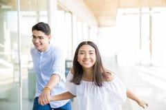 Gladlynt tonår som kör i korridor på shoppinggallerian royaltyfria bilder