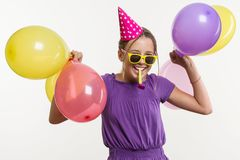 Gladlynt tonårs- flicka 12,13 gamla år, med ballonger, i den festliga hatten som blåser ett rör på vit bakgrund, Royaltyfri Fotografi