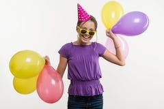 Gladlynt tonårs- flicka 12,13 gamla år, med ballonger, i festlig hatt på vit bakgrund Arkivfoto