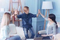 Gladlynt trycka på för barn gömma i handflatan samman med mamma och terapeut royaltyfria foton