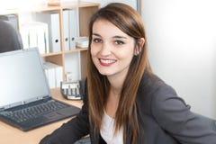 gladlynt ung affärskvinna som arbetar på bärbara datorn och ler, medan sitta på hennes skrivbordkontor royaltyfria foton