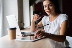 Gladlynt ung affärskvinna som i regeringsställning använder minnestavlaPC royaltyfri fotografi