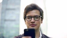 Gladlynt ung affärsman som använder smartphonen i centrum arkivfilmer