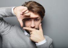 Gladlynt ung affärsman som gör en gest fingerramen royaltyfria foton
