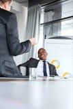 Gladlynt ung affärsman som talar med den manliga kollegan i bräderum arkivbild