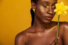 Gladlynt ung afrikansk kvinna med gul makeup på henne ögon Kvinnlig modell mot gul bakgrund med den gula blomman royaltyfri foto
