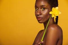 Gladlynt ung afrikansk kvinna med gul makeup på henne ögon Kvinnlig modell mot gul bakgrund med den gula blomman royaltyfri bild