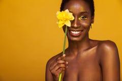 Gladlynt ung afrikansk kvinna med gul makeup på henne ögon Kvinnlig modell som skrattar mot gul bakgrund med guling fotografering för bildbyråer