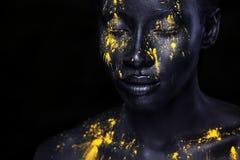 Gladlynt ung afrikansk kvinna med konstmodemakeup En fantastisk kvinna med svart makeup och att läcka gul målarfärg arkivfoto