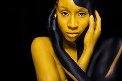 Gladlynt ung afrikansk kvinna med konstmodemakeup En fantastisk kvinna med svart- och gulingmakeup arkivbild