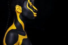 Gladlynt ung afrikansk kvinna med konstmodemakeup En fantastisk kvinna med svart- och gulingmakeup royaltyfri foto