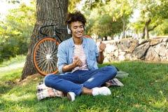 Gladlynt ung afrikansk tonåring med cykeln utomhus arkivbilder