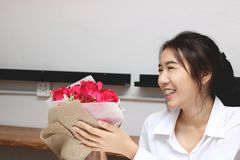 Gladlynt ung asiatisk kvinna som i regeringsställning accepterar en bukett av röda rosor från pojkvän på dag för valentin` s Förä Royaltyfria Bilder