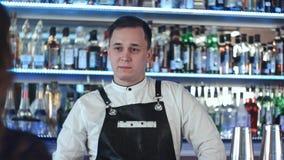 Gladlynt ung bartender som ler och talar till klienten i stång Arkivfoton