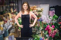 Gladlynt ung blomsterhandlareställning som är inre på den svarta tabellen Hon rymmer händer på höfter och leende på kamera Ställn arkivfoton