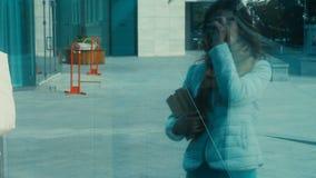 Gladlynt ung brunett i exponeringsglas med bokos i händer som ser spegelväggen stock video