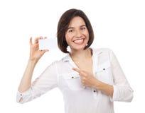 Gladlynt ung brunett som visar ett vitt affärskort Royaltyfri Bild