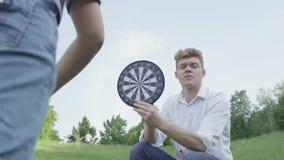 Gladlynt ung fader som rymmer pilar medan hans son som kastar pilar på en magnet i cirklarna familjfritid utomhus arkivfilmer