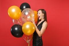 Gladlynt ung flicka i liten svart klänning som firar rymma luftballonger isolerade på röd bakgrund St-valentin` s arkivbild