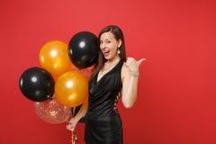 Gladlynt ung flicka i litet svart fira för klänning och att peka tummen åt sidan som rymmer luftballonger isolerade på rött royaltyfri fotografi