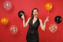 Gladlynt ung flicka i litet svart fira för klänning som visar segertecknet på ljusa röda bakgrundsluftballonger ST royaltyfri bild