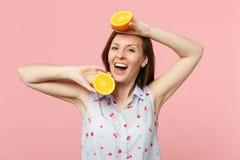 Gladlynt ung flicka i sommarkläder som rymmer två halfs av ny mogen orange frukt som isoleras på den rosa pastellfärgade väggen arkivbild