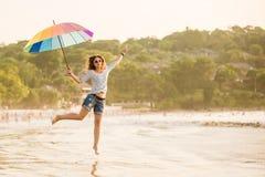 Gladlynt ung flicka med regnbågeparaplyet som det har Royaltyfri Foto