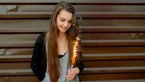 Gladlynt ung flicka som har gyckel med tomteblosset som är främst av den målade moderna väggen i brun färg stock video