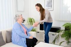 Gladlynt ung flicka som hemma tar omsorg av den gamla höga kvinnan arkivbild