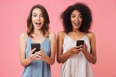 Gladlynt ung flicka två i klänningar som rymmer mobiltelefoner arkivbild