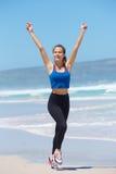 Gladlynt ung konditionkvinnaspring med lyftta armar Royaltyfria Foton