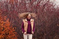 Gladlynt ung kvinna i en varm tröja i höst royaltyfri bild