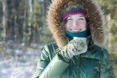 Gladlynt ung kvinna i kopp för hållande för rostfritt stål för vinterskog turist- flaska för termos utomhus arkivbild