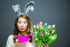 Gladlynt ung kvinna med den kaninöra- och för påskägg korgen och tulpanblommor som ser kameran arkivfoton