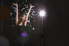 Gladlynt ung kvinna med lyftta händer som dansar och har gyckel Royaltyfri Bild