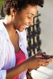 Gladlynt ung kvinna som använder mobiltelefonen Arkivfoto