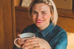Gladlynt ung kvinna som dricker varmt kaffe eller te som tycker om det, medan sitta i kaf? royaltyfri foto