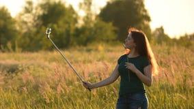 Gladlynt ung kvinna som gör selfieresande De varma signalerna ural town för bergsimsolnedgång arkivfilmer