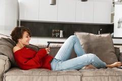 Gladlynt ung kvinna som hemma kopplar av arkivfoton