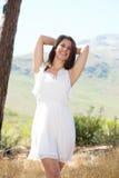 Gladlynt ung kvinna som ler i den vita klänningen i natur Arkivbilder